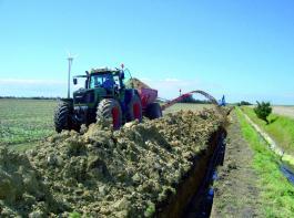 Dosieren von Sand in Kabeltrassen geht mit einem Vario-Getriebe sehr genau, am Bredal-Streuer ist dafür ein Wurfband angebaut. Foto: Serck