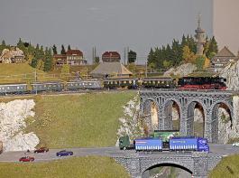 Die Dampflok schnaubt über die Ravennabrücke in den Hochschwarzwald hinauf, während parallel  der Straßenverkehr im Höllental fließt.