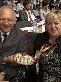 Kordula Kovac macht bei Wolfgang Schäuble Werbung für den Kirschstollen mit heimischem Kirschwasser.