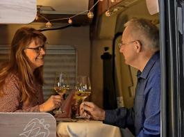 """Mit Tischdeko und Beleuchtung ist auch im Camper für Atmosphäre gesorgt. Petra Littner und ihr Mann Karlheinz freuen sich über ein serviertes Menü mit  feinem Wein in """"Camping-Atmosphäre"""" – eine neue Erfahrung."""