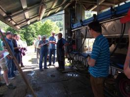 Klaus Wetzel (Bildmitte) melkt den Sommer über seine Kühe mit dem mobilen Weidemelkstand auf den Weiden rund um die Utzenfluh. Hier erklärt er den Teilnehmern der Lehrfahrt Ablauf, Handhabung und Technik seines an das Steillagengebiet angepassten Anhängers mit einem  6er-Fischgrätenmelkstand von DeLaval.
