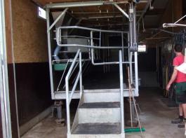 Matthias Marx aus Wembach hat diesen Weidemelkstand – wie  auch den Stall und das 'Melkstandshaus'  –  in viel erfinderischer  Eigenleistung konstruiert. Wenn die 17 Milchkühe in Hofnähe  weiden, wie zur Zeit der Lehrfahrt, oder im Winter im Stall sind,  steht der Melkstand stationär unter Dach. Sind die Kühe  auf der anderen Talseite, wird der Melkstand mitgenommen.