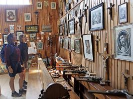 Zwei Besucherinnen staunen über Bilder, Kreuze und mehr.