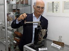 Dr. Mehdi Rashid zeigt die Funktionsweise eines Pillendrehers. Daneben eine Gießform für Zäpfchen.