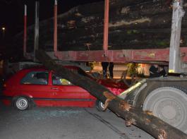 Unter dem Schwertransporter hat sich ein roter Kleinwagen verkeilt. Ein Baumstamm der Ladung ist herabgestürzt.