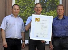 Wirtschaftsförderer Robin Derdau, Landrat Hanno Hurth und der Geschäftsführer der Wirtschaftsförderung des Kreises Emmendingen, Thorsten Kille (v.l.), mit der Urkunde zur Ernennung des Projektes als Leuchtturmprojekt Weinbau 4.0.