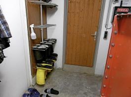 Die Stallkleidung (Overall, Schuhe) wird in der Hygieneschleuse aufbewahrt und dort vor dem Betreten des Stalls angezogen.
